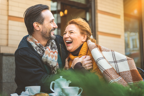 A couple laughing outdoors in the fall enjoying a relaxing couples retreat